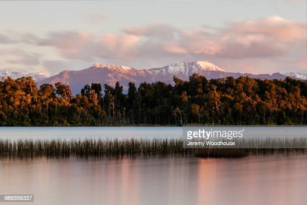 Mountains over forest and still river, Hokitika, South Westland, New Zealand