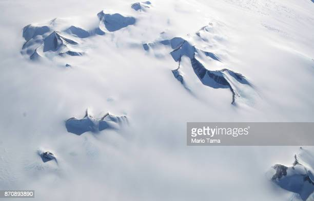 Mountains peek through land ice as seen from NASA's Operation IceBridge research aircraft in the Antarctic Peninsula region on November 4 above...