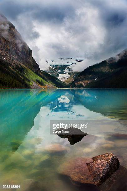 Mountains reflected in tranquil lake louise; alberta canada