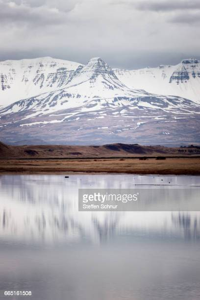 Mountains reflected in water, snow, Iceland