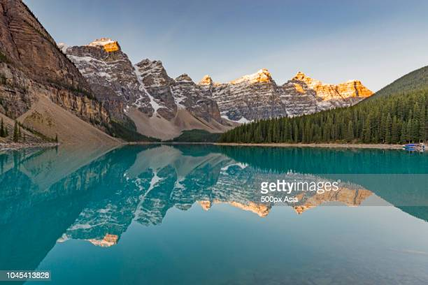 mountains reflecting in lake, canada - image stock pictures, royalty-free photos & images