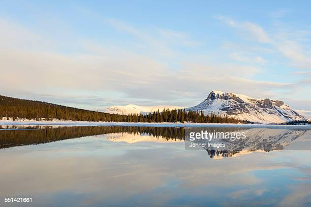 mountains reflecting in lake - swedish lapland stock photos and pictures