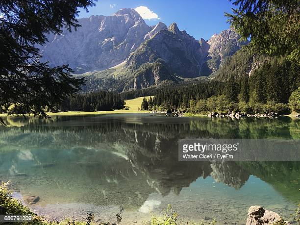 mountains reflecting on calm lake - walter ciceri foto e immagini stock