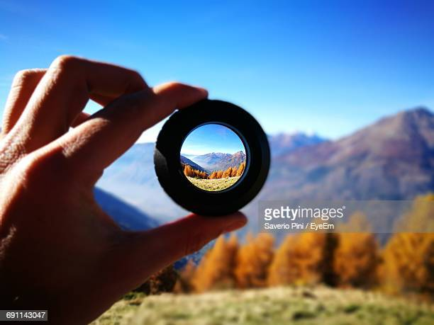 mountains seen through lens being held by person - image focus technique stock pictures, royalty-free photos & images