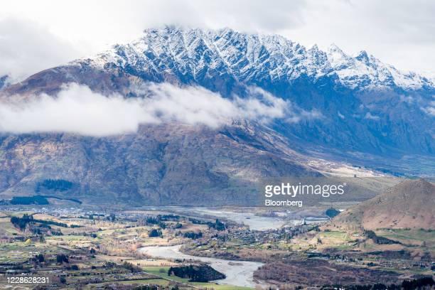 Mountains stand beyond fields in the Coronet Peak ski area near Queenstown, New Zealand, on Thursday, Sept. 10, 2020. In a normal year, international...