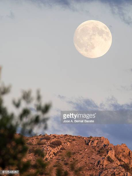 Mountaintop illuminated by sunlight at sunset with bright full moon in the blue sky