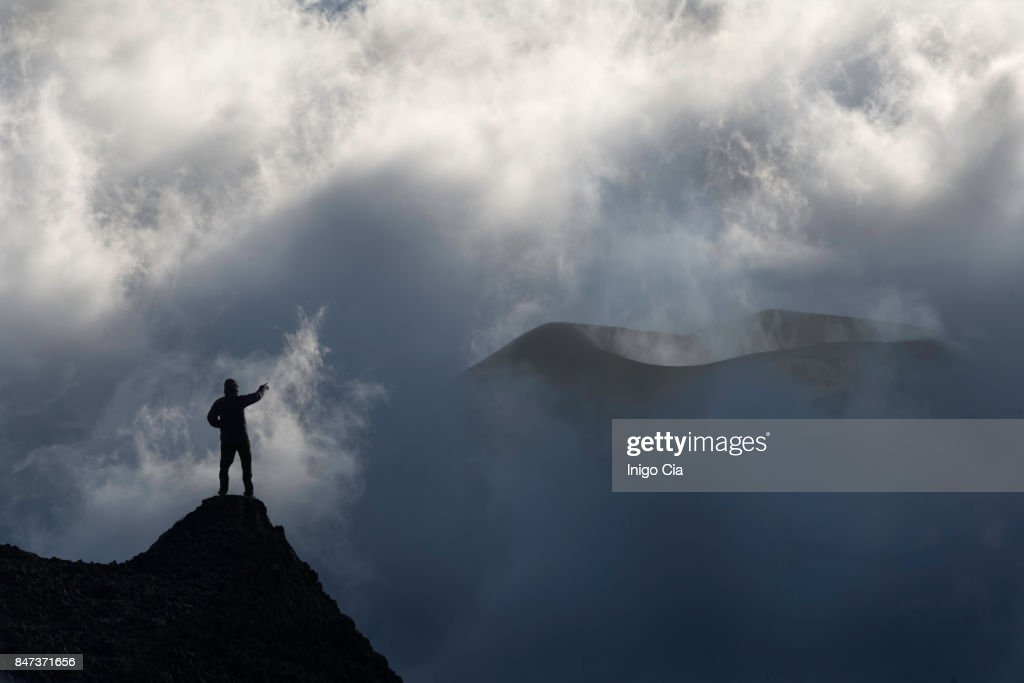 A mountanier man standing in front of a volcano : Stock Photo