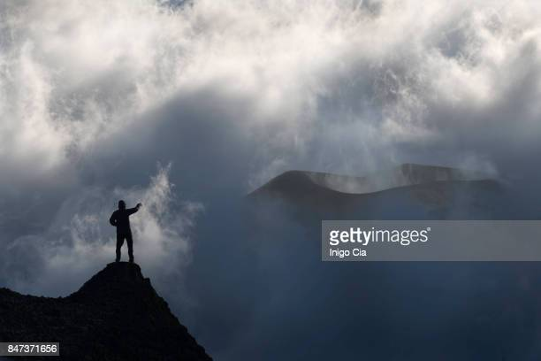 A mountanier man standing in front of a volcano
