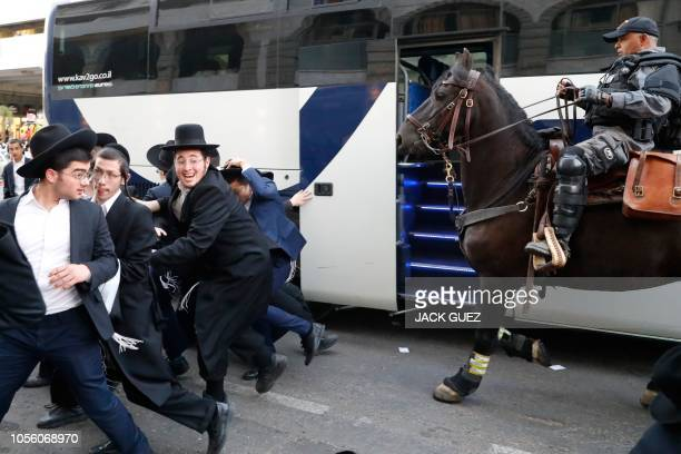 A mounted Israeli policeman disperses a group of UltraOrthodox Jews during a demonstration against Israeli army conscription in the Israeli city of...