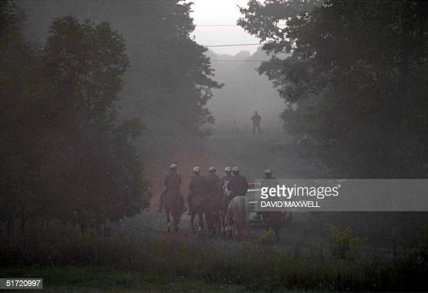 Mounted police make their way along an access road leading to the crash site of United Airlines Flight 93 through the early morning fog 12 September...