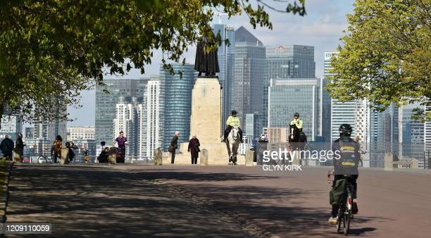 Mounted police monitor people taking excercise with the London skyline in the background at Greenwich Park in south London on April 4 as life...