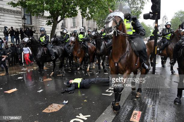 Mounted police officer lays on the road after being unseated from their horse, during a demonstration on Whitehall, near the entrance to Downing...