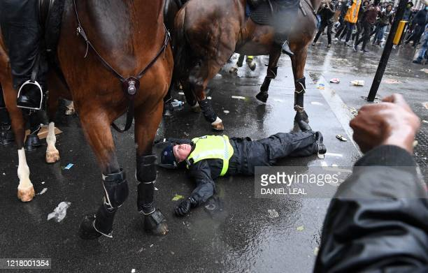 A mounted police officer lays on the road after being unseated from their horse during a demonstration on Whitehall near the entrance to Downing...