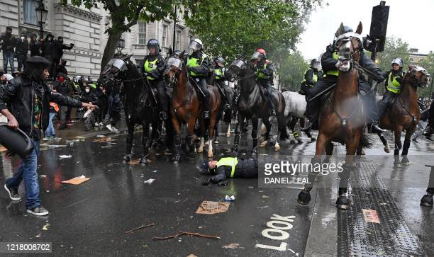 Mounted police officer lays on the road after being unseated from their horse on Whitehall, near the entrance to Downing Street in central London on...