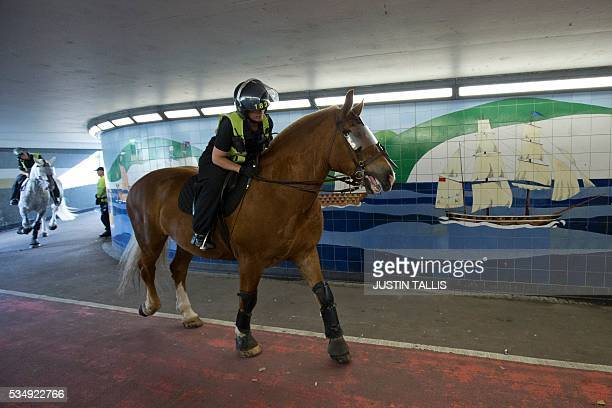 A mounted police officer lowers her head while going through an underpass during a march by a group of far right demonstrators in the town of Dover...