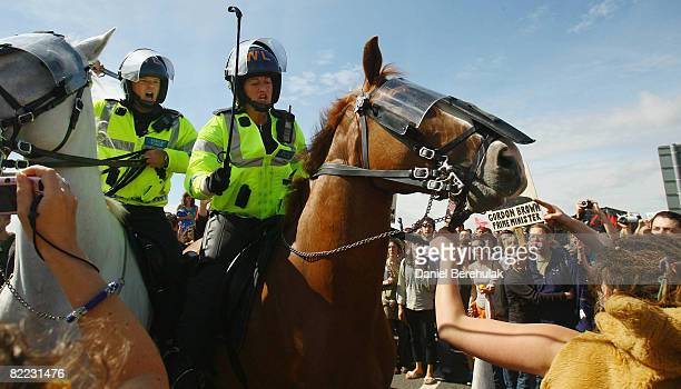 A mounted police officer raises her riding crop as an activist grabs hold of the reins of her horse during a march by protestors towards Kingsnorth...