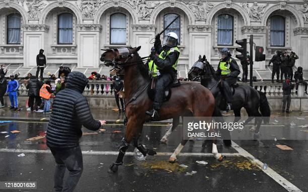 Mounted police officer raises their baton as police horses ride along Whitehall, past the entrance to Downing Street, in an attempt to disperse...