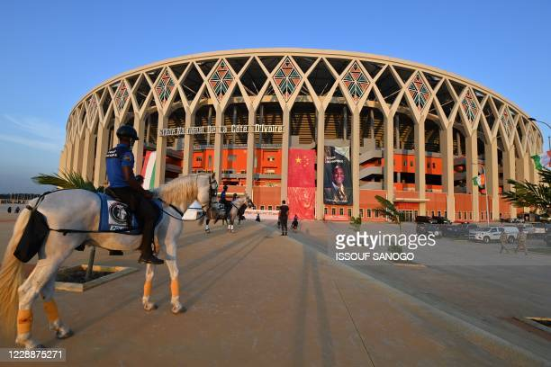 Mounted police officer stands outside Ivory Coast's newly inaugurated 60,000-seat Olympic stadium, built with the help of China, in Ebimpe, outside...