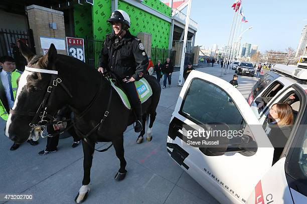 TORONTO ON MAY 13 A mounted police officer walks by CP24 reporter Jackie Crandles Maple Leafs Sports and Entertainment provides additional security...