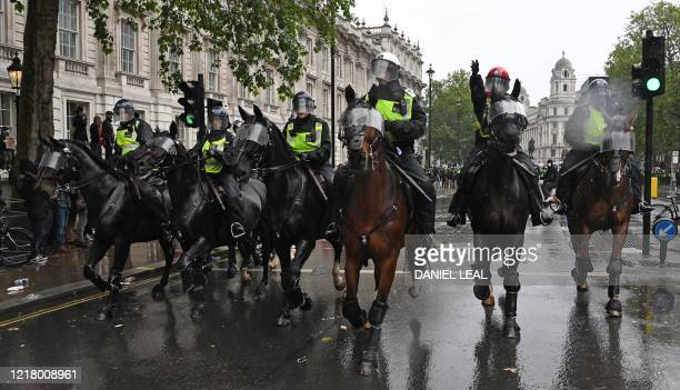 Mounted police officers charge their horses along Whitehall past the entrance to Downing Street in an attempt to disperse protestors gathered in...