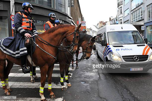 Mounted police officers patrol in a street in the local Congolese community in the Matonge district in Brussels on December 20 2011 after protests...