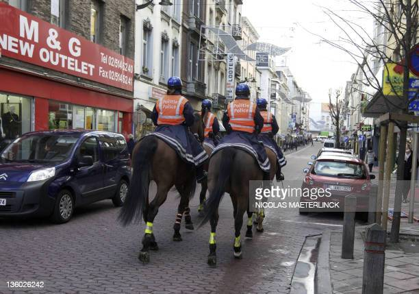 Mounted police officers patrol in the local Congolese community in the Matonge district in Brussels on December 20 2011 after protests broke out last...