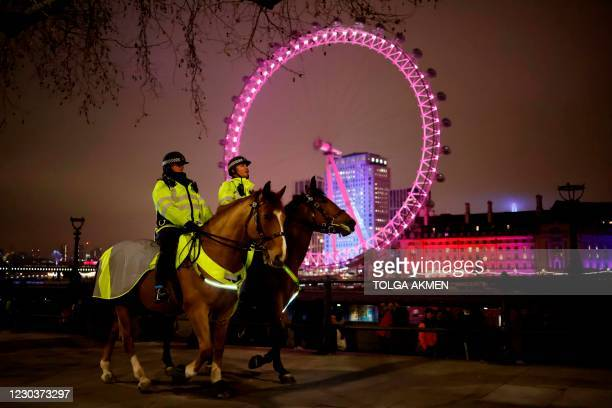 Mounted police officers patrol The Victoria Embankment opposite the London Eye in a near-deserted London late on New Year's Eve, December 31 as...