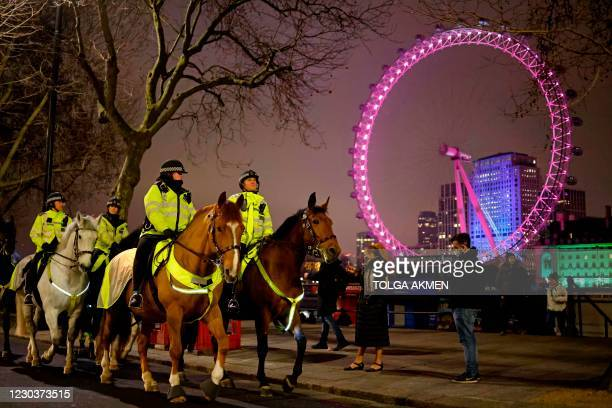 Mounted police officers patrol The Victoria Embankment opposite the London Eye in a near-deserted London on New Year's Eve, December 31 as...