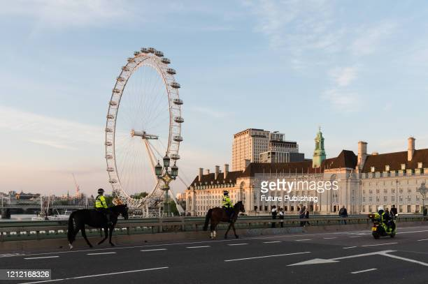 Mounted police officers ride across Westminster Bridge during the weekly 'Clap for our Carers' applause for the NHS and key workers on the front line...