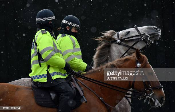 Mounted Police officers ride their horses through the snow in London on February 9, 2021. - Cold weather swept across northern Europe bring snow and...