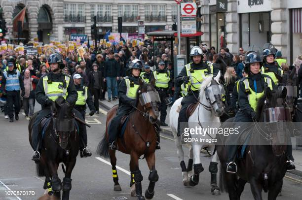 Mounted police officers stand in front of the march against Tommy Robinson Thousands of people took to the streets in central London to march against...