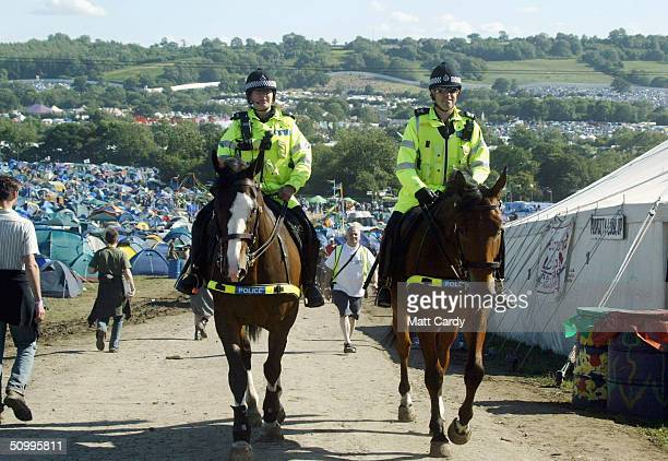 Mounted police patrol the site area on June 25 2004 at Worthy Farm Pilton Somerset at the 2004 Glastonbury Festival The music festival spans over 3...