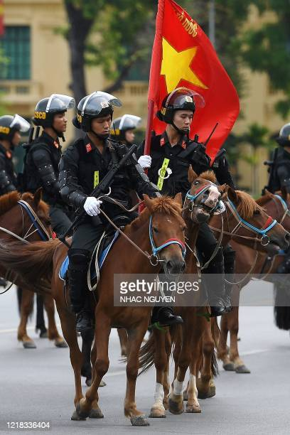 Mounted police personnel parade on horses past the Ho Chi Minh mausoleum in Hanoi on June 8, 2020.