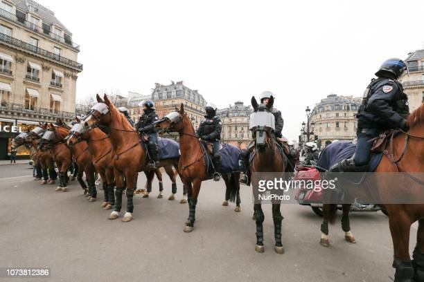 Mounted police units take security measures at the place de l'Opera in front of the Opera Garnier in Paris on December 15 during a demonstration...