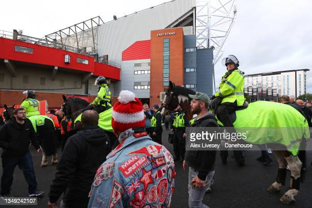 Mounted police watch supporters of Manchester United and Liverpool prior to the Premier League match between Manchester United and Liverpool at Old...