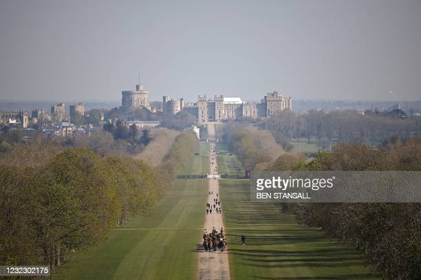 Mounted regiment of the British Army exercise their horses along The Long Walk, leading to Windsor Castle in Windsor Great Park, west of London, on...