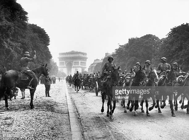 Mounted soldiers of the Wehrmacht ride down a Paris street away from the well known Arc de Triumph June 1940