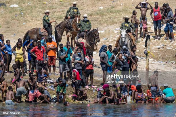 Mounted U.S. Border Patrol agents watch Haitian immigrants on the bank of the Rio Grande in Del Rio, Texas on September 20, 2021 as seen from Ciudad...