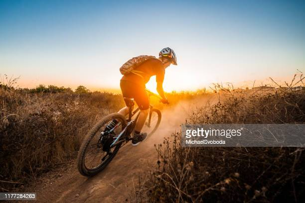 mountian biker riding into the sunset - cross country cycling stock pictures, royalty-free photos & images