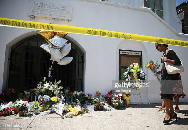 Mourner adds flowers to a memorial in front of Emanuel AME Church on June 18, 2015 in Charleston, South Carolina. Nine people were killed on June 17...