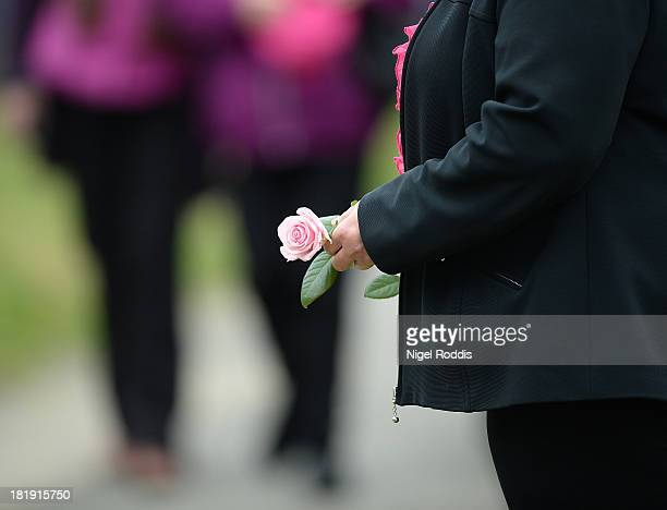 A mourner carries a pink rose as they arrive for the funeral service of murdered schoolgirl April Jones at St Peter's Church Machynlleth on September...