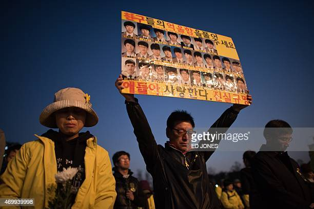 A mourner carries a placard festuring portraits of the victims of the Sewol ferry during a rally to mark the first anniversary of the disaster in...
