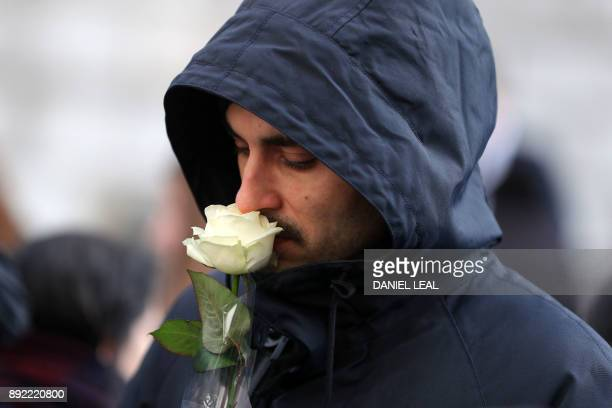 A mourner carries a white rose as he leaves after attending the Grenfell Tower National Memorial Service at St Paul's Cathedral in London on December...