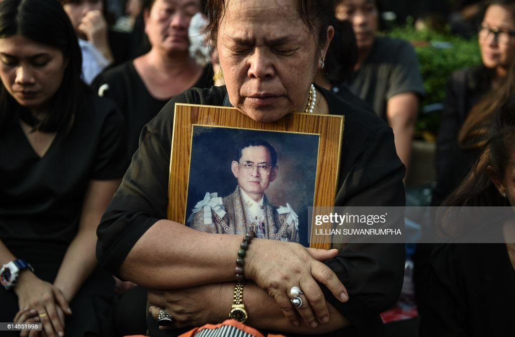 TOPSHOT - A mourner clutches a picture of Thai King Bhumibol Adulyadej after the hearse carrying the body of the late monarch passes the Grand Palace in Bangkok on October 14, 2016. Bhumibol, the world's longest-reigning monarch, passed away aged 88 on October 13, 2016 after years of ill health, removing a stabilising father figure from a country where political tensions remain two years after a military coup. / AFP / LILLIAN