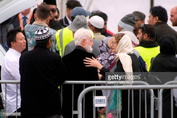 A mourner comforts John Milne father of 14yearold Sayyad Milne one of 50 people killed in New Zealands twin mosque massacre during the funeral...