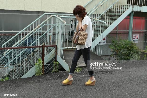 A mourner cries as she visits the scene where over 30 people died in a fire at the Kyoto Animation company building in Kyoto on July 19 2019 Details...