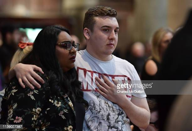 A mourner dressed in a Marvel comic tshirt comforts another mourner as they attend the funeral service of journalist Lyra McKee at St Anne's...