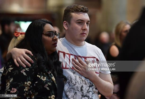 A mourner dressed in a Marvel comic tshirt comforts another mourner at the funeral service of journalist Lyra McKee who was killed by a dissident...