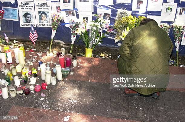 Mourner grieves in front of the makeshift memorial site dubbed the Wall of Prayers which has sprung up in front of Bellevue Hospital on First Ave...