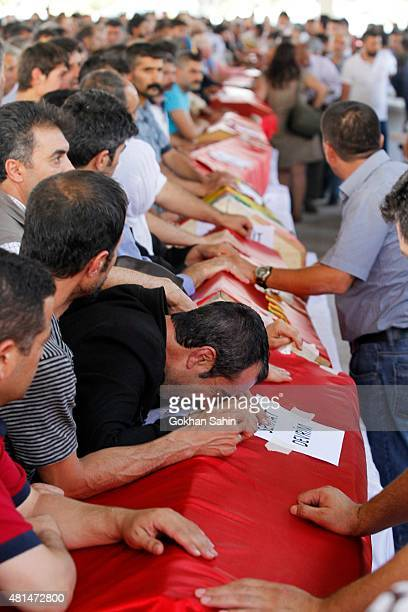 A mourner grieves over a coffin during a funeral ceremony for the victims of a suicide bomb attack yesterday which killed 32 people in the southern...